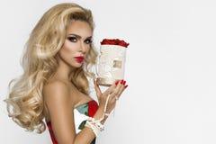 Mujer rubia hermosa en un vestido de noche elegante con las rosas rojas, sosteniendo el regalo de una tarjeta del día de San Vale foto de archivo