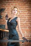 Mujer rubia hermosa joven del pelo corto en el vestido negro que fuma un cigarrillo Señora misteriosa romántica elegante con mira Fotografía de archivo