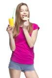 Mujer rubia hermosa joven que bebe el zumo de naranja Imagen de archivo libre de regalías