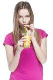 Mujer rubia hermosa joven que bebe el zumo de naranja Foto de archivo libre de regalías