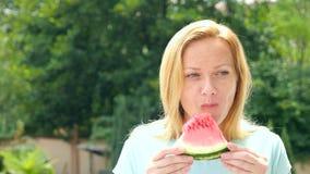 Mujer rubia hermosa joven que come la sandía al aire libre contra el cielo y los árboles 4K Cámara lenta almacen de video