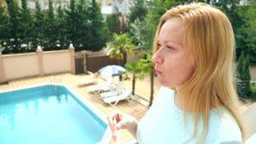Mujer rubia hermosa joven que come la sandía al aire libre contra el cielo y los árboles 4K Cámara lenta metrajes