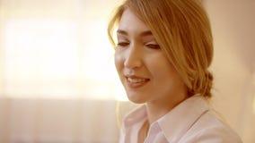 Mujer rubia hermosa joven que da vuelta principal y que sonríe en la cámara