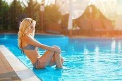 Mujer rubia hermosa joven que descansa en la piscina imagenes de archivo