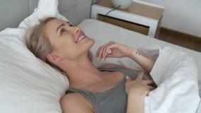 Mujer rubia hermosa joven que duerme en su dormitorio almacen de video