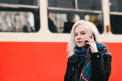 Mujer rubia hermosa joven que habla en el teléfono en un fondo de la estación de tren roja Retrato al aire libre de una muchacha Imágenes de archivo libres de regalías