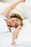 Mujer rubia hermosa joven que miente en la cama que intenta despertar fotografía de archivo