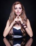 Mujer rubia hermosa joven que se sienta en la tabla del espejo en vagos negros Fotos de archivo