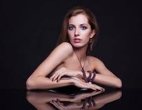 Mujer rubia hermosa joven que se sienta en la tabla del espejo en vagos negros Imagen de archivo libre de regalías