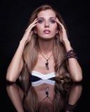 Mujer rubia hermosa joven que se sienta en la tabla del espejo en vagos negros Imagen de archivo