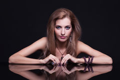 Mujer rubia hermosa joven que se sienta en la tabla del espejo en vagos negros Fotografía de archivo