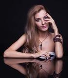 Mujer rubia hermosa joven que se sienta en la tabla del espejo en vagos negros Foto de archivo