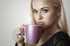 Mujer rubia hermosa que bebe Coffee.Cup del té. Bebida caliente Imágenes de archivo libres de regalías