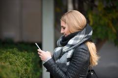 Mujer rubia hermosa que camina y que manda un SMS en el teléfono celular Fotografía de archivo libre de regalías