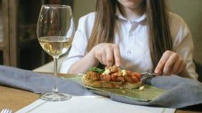 Mujer rubia hermosa que come y que bebe en el restaurante, hora de la almuerzo almacen de video
