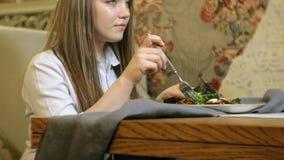 Mujer rubia hermosa que come y que bebe en el restaurante, hora de la almuerzo almacen de metraje de vídeo
