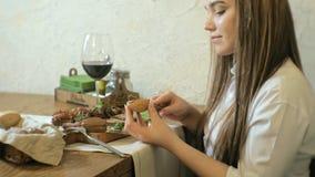Mujer rubia hermosa que come y que bebe en el restaurante, hora de la almuerzo metrajes