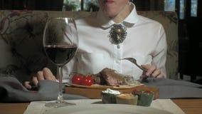 Mujer rubia hermosa que come y que bebe en tiempo del restaurante, del almuerzo o de cena metrajes
