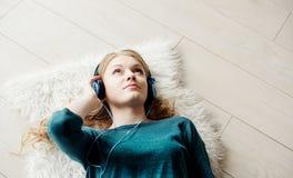 Mujer rubia hermosa que escucha la música a través de los auriculares Fotografía de archivo libre de regalías
