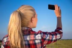 Mujer rubia hermosa que hace la foto del selfie en smartphone Imagen de archivo