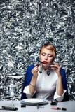 Mujer rubia hermosa que hace maquillaje en la tabla de cena contra del fondo conceptual de plata Imagenes de archivo