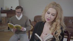 Mujer rubia hermosa que lee el libro en el primero plano mientras que hombre modesto vestido que estudia el material en el fondo metrajes