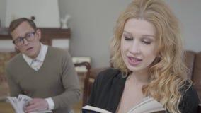 Mujer rubia hermosa que lee el libro en voz alta en el primero plano mientras que hombre modesto vestido que estudia el material  almacen de video