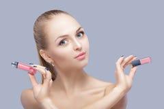 Mujer rubia hermosa que lleva a cabo lustre rosado del labio en fondo gris Maquillaje del labio foto de archivo libre de regalías