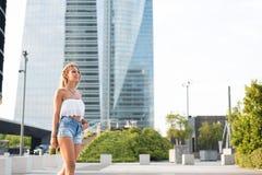 Mujer rubia hermosa que lleva los vaqueros cortos que caminan en la calle Foto de archivo libre de regalías