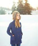Mujer rubia hermosa que lleva una chaqueta de la capa con la capilla sobre nieve en invierno Fotografía de archivo libre de regalías