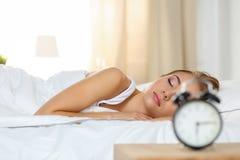 Mujer rubia hermosa que miente pacífico en dormir de la cama Fotos de archivo libres de regalías
