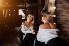Mujer rubia hermosa que mira su reflexión en el espejo en salón de belleza y que comprueba nuevos corte de pelo y maquillaje Saló imagen de archivo
