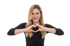 Mujer rubia hermosa que muestra la muestra del corazón con sus manos Fotografía de archivo libre de regalías