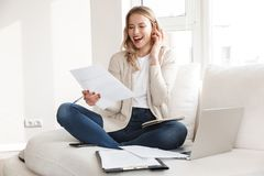 Mujer rubia hermosa que plantea sentarse dentro en casa usando el ordenador portátil que habla por el teléfono móvil imagen de archivo