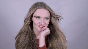 Mujer rubia hermosa que presenta en estudio en vestido rojo Mirada atractiva Cámara lenta almacen de video