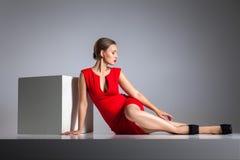 Mujer rubia hermosa que presenta en vestido rojo foto de archivo