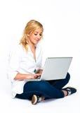 Mujer rubia hermosa que pulsa en la computadora portátil Fotografía de archivo