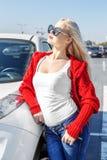 Mujer rubia hermosa que se coloca cerca de su coche en gafas de sol Concentrado imagen de archivo libre de regalías