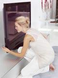 Mujer rubia hermosa que se sienta cerca de la TV Imagen de archivo libre de regalías