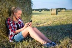 Mujer rubia hermosa que se sienta cerca de pajar en campo con mobil Fotos de archivo libres de regalías