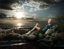 Mujer rubia hermosa que se sienta cerca del mar Fotos de archivo