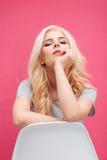 Mujer rubia hermosa que se sienta en la silla Imagenes de archivo