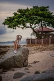 Mujer rubia hermosa que se sienta en una roca por el mar y que escucha la música con su tableta Manos con los tatuajes estilo Fotos de archivo