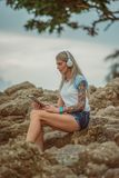 Mujer rubia hermosa que se sienta en una roca por el mar y que escucha la música con su tableta Manos con los tatuajes estilo Foto de archivo