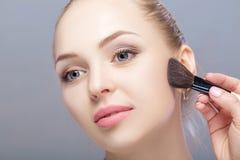 Mujer rubia hermosa que sostiene el cepillo del maquillaje en un fondo gris Mujer que aplica blusher imagen de archivo