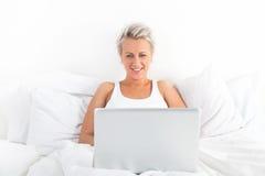 Mujer rubia hermosa que usa un ordenador portátil y una sonrisa Imágenes de archivo libres de regalías
