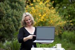 Mujer rubia hermosa sonriente que señala en la computadora portátil Foto de archivo