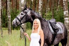 Mujer rubia hermosa y caballo gris en bosque Fotos de archivo libres de regalías