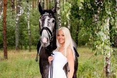 Mujer rubia hermosa y caballo gris en bosque Foto de archivo