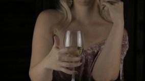 Mujer rubia impaciente joven que bebe el vino rojo y que espera una fecha en café Cámara lenta almacen de video